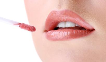 Beautiful young woman applying lip gloss, close up.