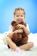 cute little girl playing with toy bear, on blue background
