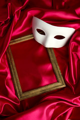 White mask and empty frame on red silk fabric