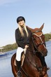 Happy blonde woman riding horse