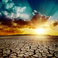 global warming. dramatic sunset over cracked earth