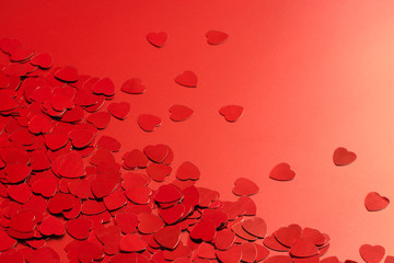 Red heart confetti on red background