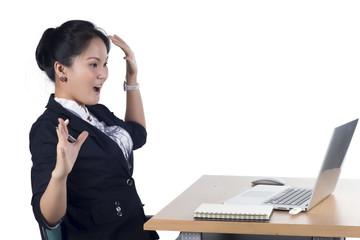 Surprised woman looking in screen of laptop