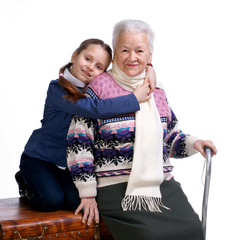 Pretty girl sitting on a box and hugging her grandmother