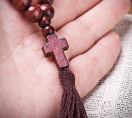 wooden rosary and a Christian cross in his hand