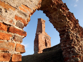 The ruins of the old castle and tower of bricks on a background
