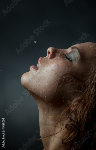 Portrait of a girl's face which water flows