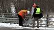 Road workers  trying to fix the bridge defence barriers