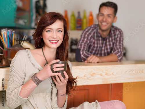 red haired girl smiling in a cafe