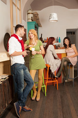 young man courting a blonde girl in colorful cafe