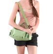 A young woman carrying a green canvas handbag