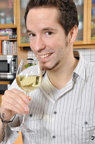Junger Mann trinkt Weißwein