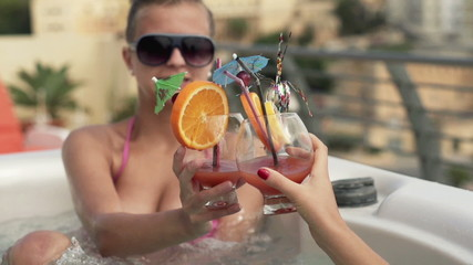 Girlfriends raising toast with drinks in hot tub, slow motion