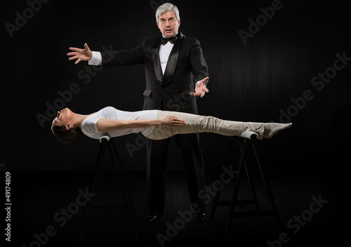 Portrait of professional hypnotist on black background working w