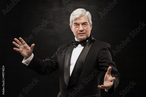 Portrait of professional hypnotist on black background