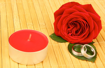 rose with wedding rings and red candle