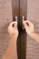 female hands opening closet door