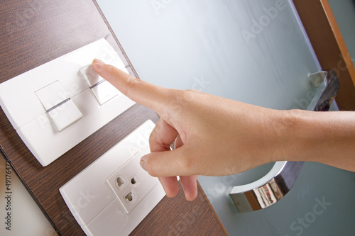 female hand turn on white electricity switch