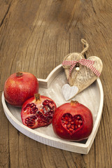 Granatäpfel und ein Herz aus Holz