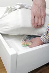 Mann versteckt Bargeld im Bett