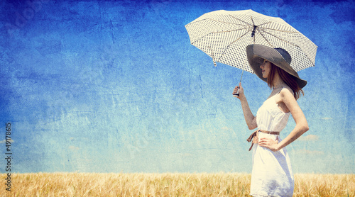 Women with umbrella at wheat field.