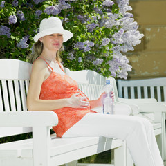 pregnant woman with bottle of water sitting on bench