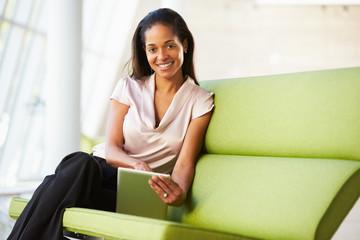 Businesswoman Sitting In Modern Office Using Digital Tablet