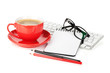 Red coffee cup, glasses and office supplies