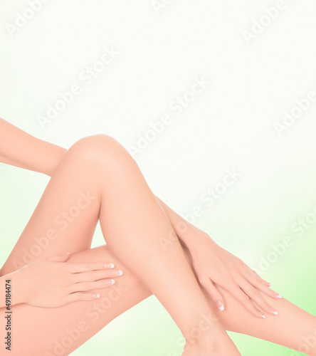 Female legs on green blurred background