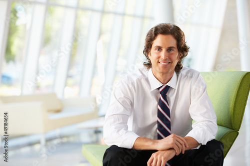 Businessman Sitting On Sofa In Modern Office