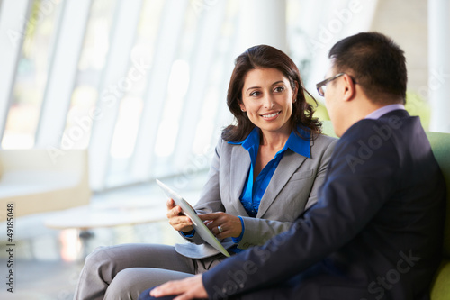 Business people With Digital Tablet Sitting In Modern Office