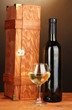 Wooden case with wine bottle on wooden table on brown