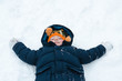 Little boy playing snow angels