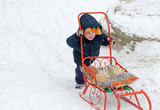 Little boy pushing his sled in snow