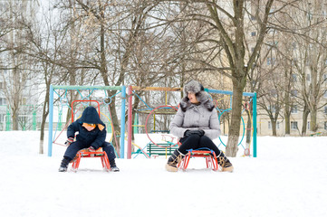 Mother and son sledding in winter