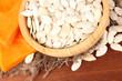 Pumpkin seeds in wooden bowl, on wooden background