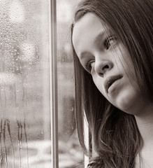 Stunning photo of a young girl gazing through a rainy window