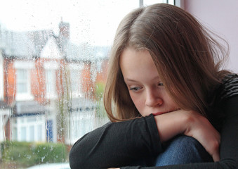 A young girl sad on her window close to tears