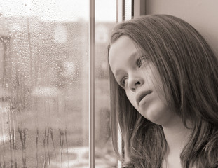 A young girl gazing out of a window on a rainy day