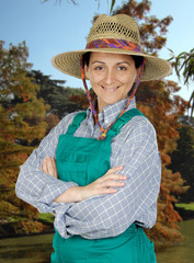 Attractive gardener woman with a straw hat