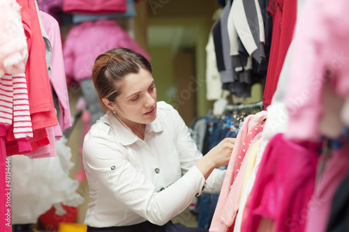 Female buyer  chooses children's clothes