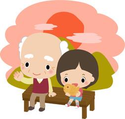 夕方にベンチに座るおじいさんと小さい女の子