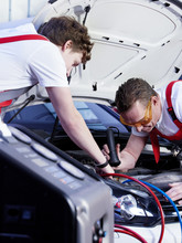 Two motor mechanic checking the air handling unit of a car