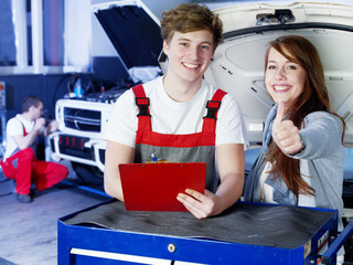 Motor mechanics and customer in garage show thumbs up