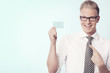Happy businessman pointing finger at blank card.