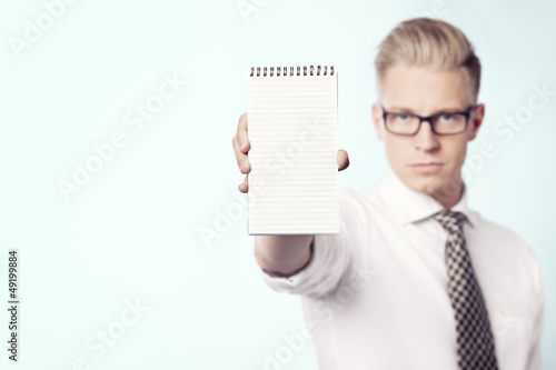 Businessman presenting blank notebook.