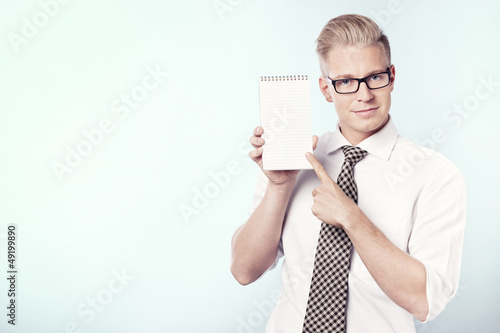 Smiling businessman pointing finger at blank notebook.