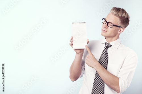 Businessman looking and pointing finger at empty notepad.
