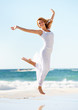 Happy young woman in white jumping in the air with the ocean beh
