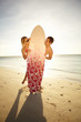 Cute young couple playing peek-a-boo around a surfboard